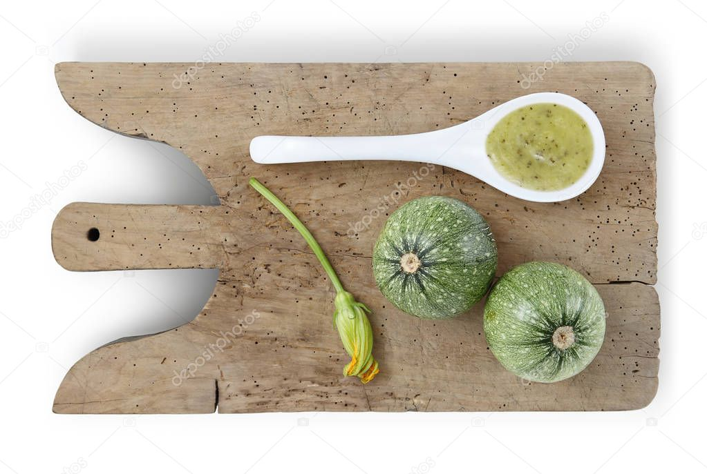 zucchini on wooden cutting board, flower and spoon of sauce food