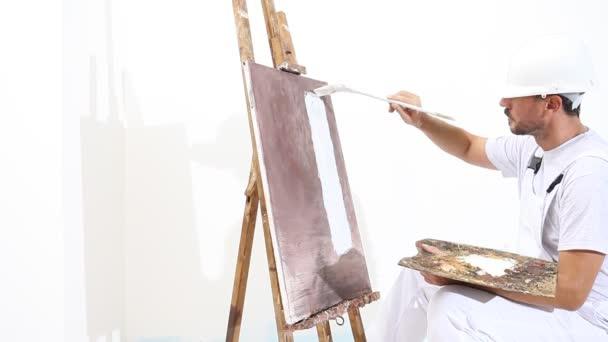 Maler Mann bei der Arbeit mit Pinsel, Staffelei, Leinwand und Palette, Wandbemalung Konzept, weißer Kopierraum Hintergrund