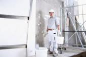 Gipser Mann Arbeit hält einen Eimer und verwenden Sie die Bürste nass die Wand vor der Anwendung auf die Innenbaustelle tragen Helm und Schutzhandschuhe, Leiter und Gerüst auf dem Hintergrund