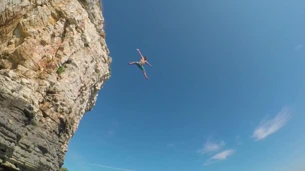 Zpomalený pohyb pod vodou: Šťastný muž, skokem z útesu vysoká oceánu do mořské vody