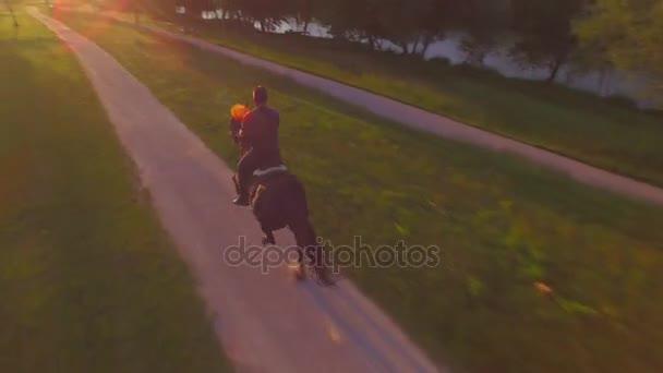 AERIAL: Senior cowboy horseback riding dark brown horse in nature at sunset