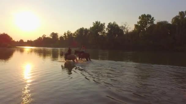 Zblízka: Dva přátelé na tmavé a světlé koně pěšky směrem k magický západ slunce