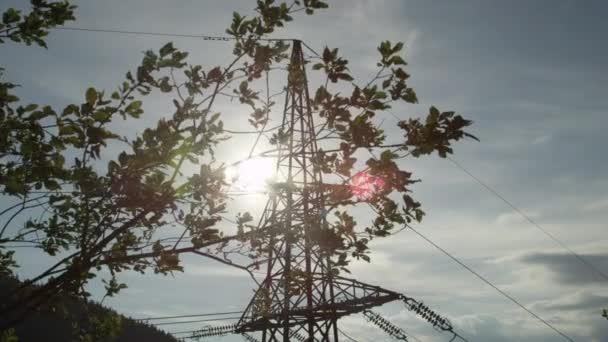 Zeitlupe: Tall Hochspannung Stahl Fernmeldeturm hinter üppigen Ast