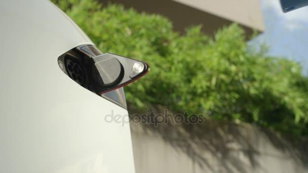 Zblízka: Mladý muž nabíjení luxusní bílý Tesla elektromobil doma