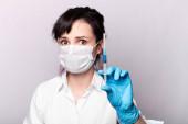 fehér inges lány, orvosi maszk és kesztyű, kék folyadékkal a kezében tartja a fecskendőt.