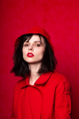 girl in red clothes with red lipstick on her lips, red background