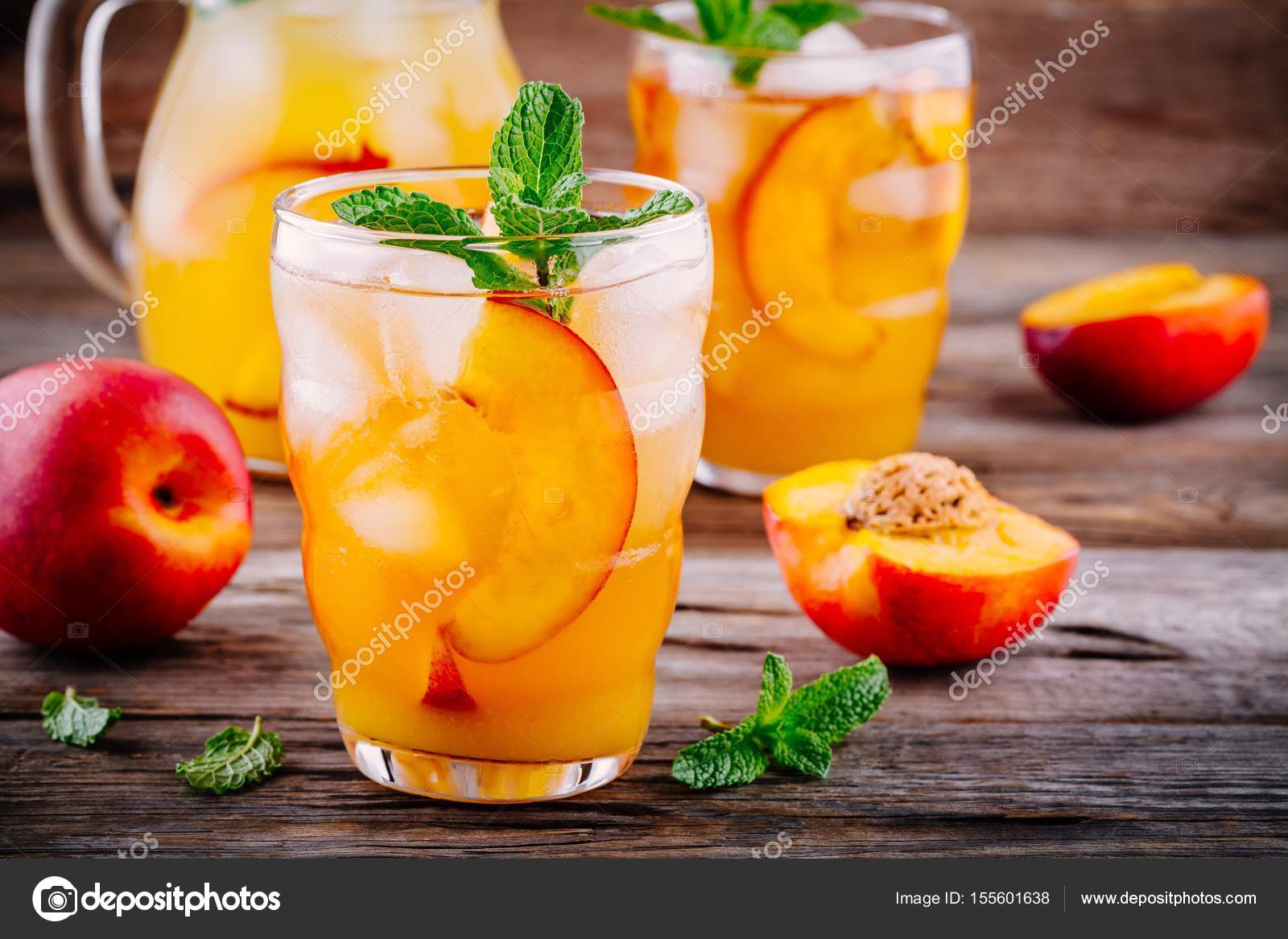 summer cold drinks homemade peach ice tea with ice cubes and mint