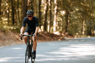 Happy bearded person in protective helmet, mirrored glasses and activewear biking on paved road in green forest during summer days. Concept of regular training and healthy lifestyle.
