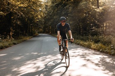 Active bearded athlete in sport clothing riding bike on paved road during sunny days. Strong sportsman in protective helmet and glasses training regularly outdoors.