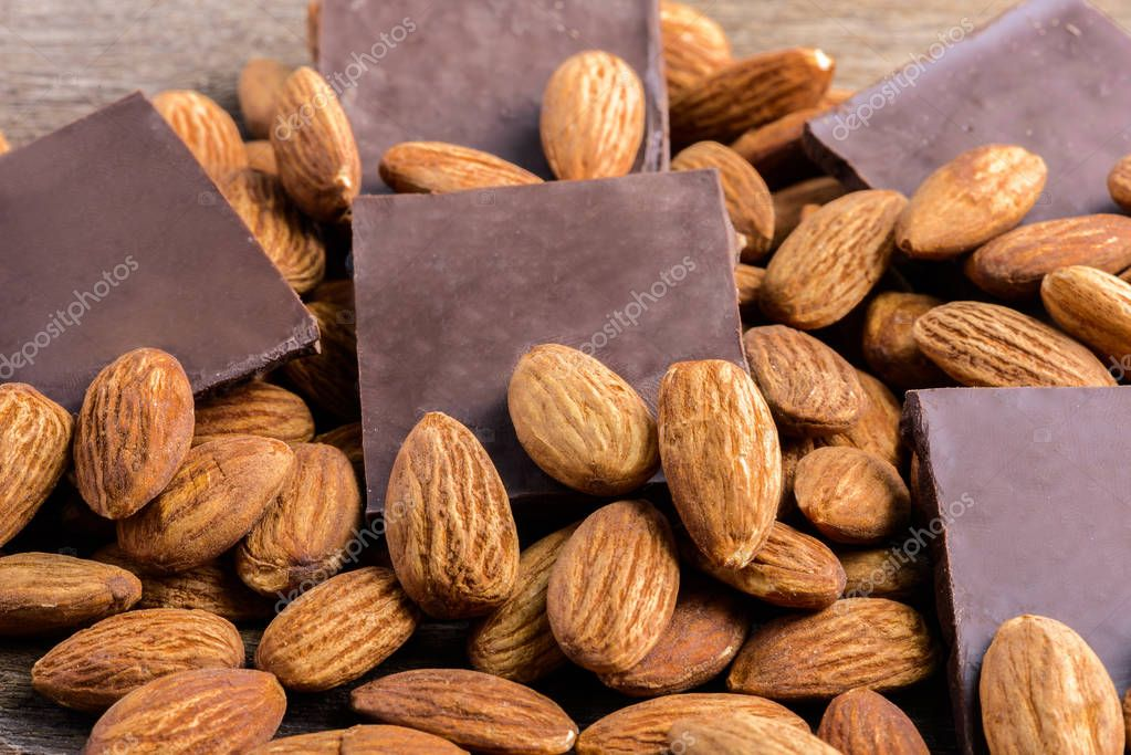 chocolate with almond on wooden background