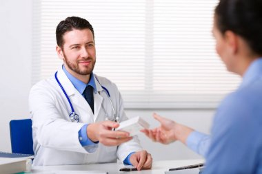 Doctor passing medicine to patient