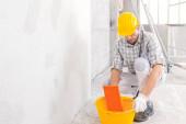 Bauarbeiter dämpft einen Schwamm in einem Eimer Wasser, um die Oberfläche einer neu verputzten Innenwand in einer Nahaufnahme mit dem Werkzeug und seinen behandschuhten Händen zu glätten
