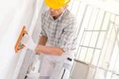 Bauarbeiter glätten neuen Putz an einer Innenwand mit einem feuchten Schwammwerkzeug in Vorbereitung auf Schleifen und Streichen bei Reparaturen oder Renovierungen