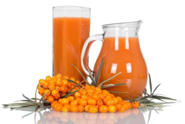 A pile of ripe sea-buckthorn berries, leaves, jug and glass