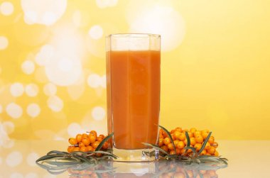 A glass of juice and a bunch of sea buckthorn berries on abstract yellow background.