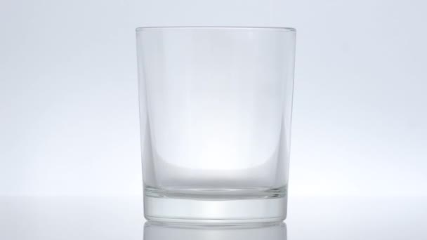 nalévání bílého nápoje jogurt, mléko, kefír do sklenice, bílé pozadí. zavřít makro