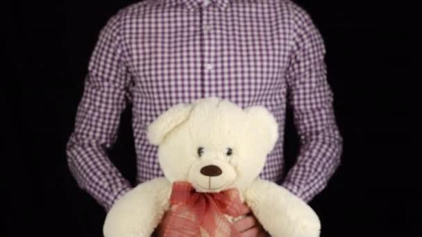 férfi orgona ing ad egy ajándék puha játék medve fekete háttér. Gratulálunk Boldog Új Évet, Boldog Karácsonyt, Boldog Valentin-napot, ajándékokat