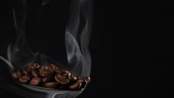 Kaffeebohnen mit Rauch in schwarzem Löffel rösten. schwarzer Hintergrund