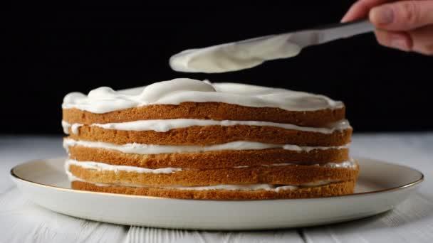 séf cukrász simítja fehér krém keksz torta. fehér lemez fekete háttér. közelkép