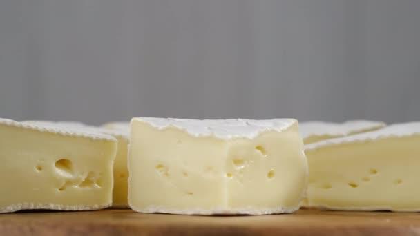 Kusy měkkého sýra Camembert. světle šedé pozadí. Lahodné kousky bílých forem s měkkými texturami Camembert zblízka, makro
