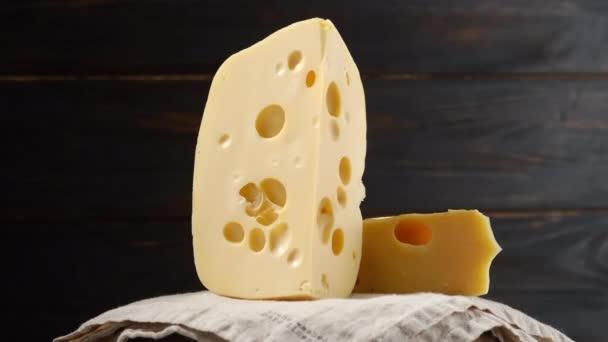 kousky tvrdého sýra s otvory na tmavém dřevěném pozadí, rotace. ubrus z plátna