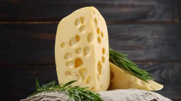 pieces of hard cheese with holes and sprig of fresh green rosemary on dark wooden background, rotation. linen tablecloth