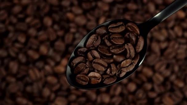 kávová zrna v černé lžičce. kávová zrna na pozadí rotace vlevo. pohled shora