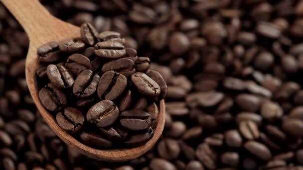 kávová zrna v černé lžičce a na pozadí. rotující
