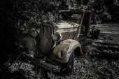 Photo A greyscale shot of an old retro car in the forest during daytime