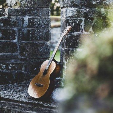 Beautiful closeup shot of a guitar placed next to a wall