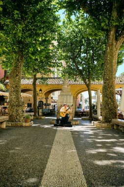 A vertical shot of a person playing guitar by the trees captured in Menton, French Riviera, France