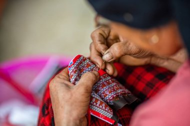 A high angle shot of a middle-aged female with damaged hands making a traditional Vietnamese clothing