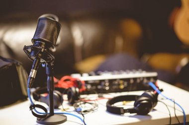 Microphone in a studio surrounded by equipment under the lights with a blurry background