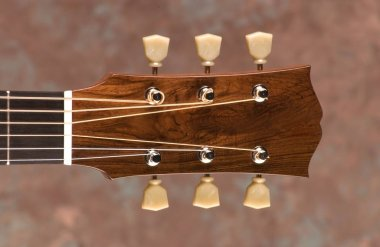 A closeup of a brown acoustic guitar headstock under the lights against a blurry background