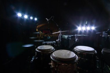 Landscape shot of an old drum set with white spotlights in the background