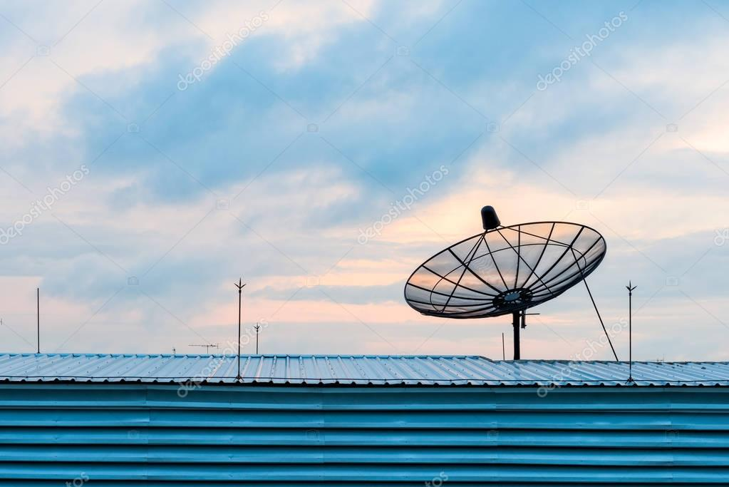 Satellite dish transmission data on background sunrise
