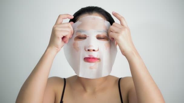 Ennek arcpakolás lapot a tisztító maszk az arcán, fehér háttér, fiatal nő