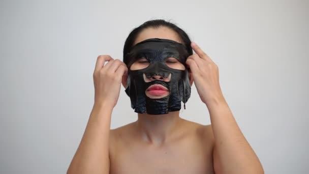 Ennek a tisztító maszk az arcán, fehér alapon fekete arcpakolás lap fiatal nő