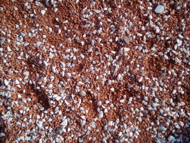 Fine decorative color granite crushed stone. Red-brown colored stone chips are used for landscaping. Crushed marble, granite, gravel or sand. Spots of fine white pebbles on heterogeneous soil