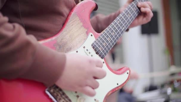 Közelkép egy férfiról, aki egy ereklye elektromos gitáron játszik egy utcai koncerten. Lassú mozgás. Rögzítés