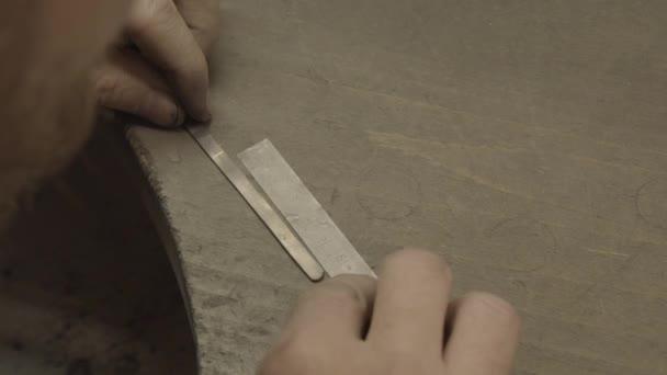 zlatník měřící kus zlata před vytvořením prstenu
