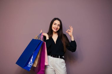 Happy young woman wearing blouse standing isolated on purple background carrying shopping bags showing okay gestures.