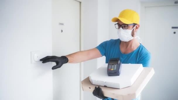 Dodavatel s ochrannou lékařskou maskou drží pizza box a POS bezdrátový terminál pro platby kartou - dny virů a pandemie, dodávky potravin do vašeho domova a bezpečnostní hygienická opatření.