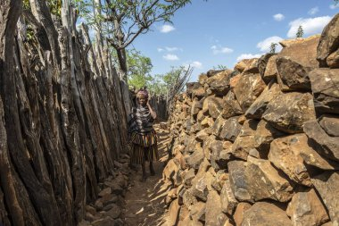 Gamole, Ethiopia - January 23: Unidentified woman walking among the defensive walls of one of the streets of a village of the Konso tribe January 23, 2018 in Gamole, Ethiopia.