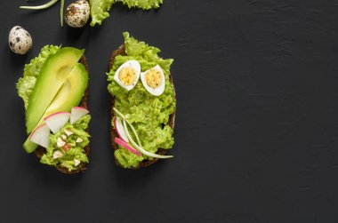 Avocado toasts on rye bread with sliced avocado for healthy breakfast on  dark black stone background. Vegetarian food. Top view, Copy space