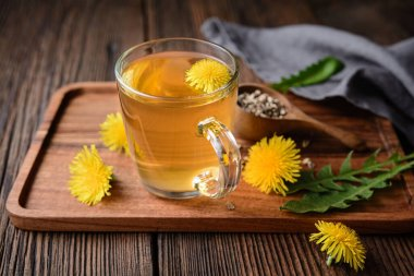 Herbal drink for liver detox, dandelion root tea in a glass cup decorated with fresh flowers on a rustic wooden background