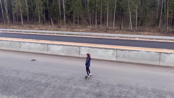 Krásná mladá žena jede sama po dálnici na vznášedle směrem k západu slunce. Volný pohyb v dopravě v životním prostředí. Snímek sledování dronů