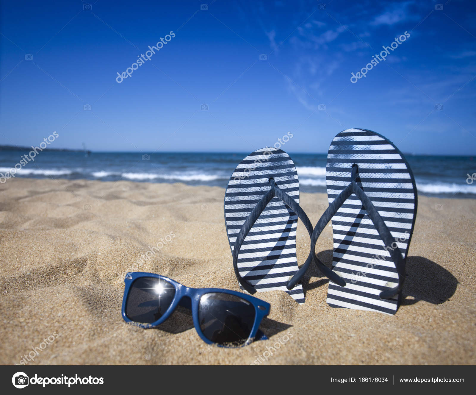 f0f23315cdff1 Blue sandal flip flop and sunglasses on the sand beach with blue sea and  sky background in summer vacation. Copy space.