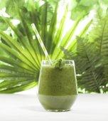 Čerstvě prolnutých zelené smoothie ve sklenici se slámou. Zelené listy pozadí