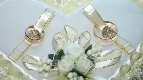 wedding rings of brides on a pillow in the form of heart